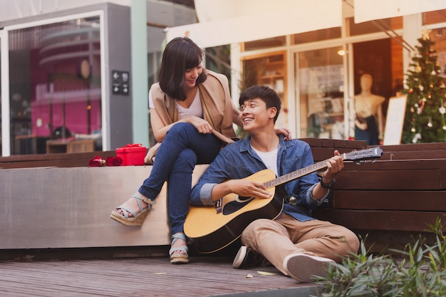 Man in love playing guitar sitting on the floor at his girlfriend