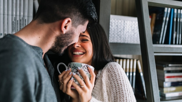 Man loving her smiling woman holding coffee cup