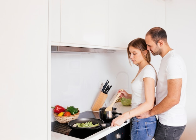 Man loving his wife coking food on new electric stove with induction cooktop in kitchen