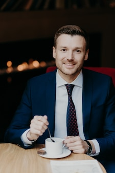 Man in luxury suit, drinks coffee, sits at wooden table in cafeteria, has pleasant smile and attractive look