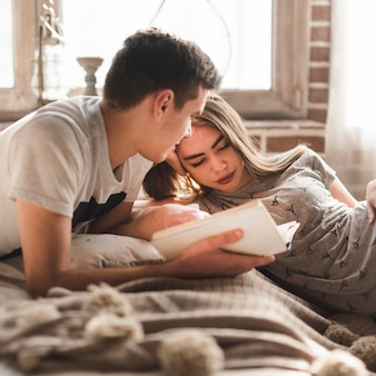 Man lying on bed looking at woman holding book in hand at home