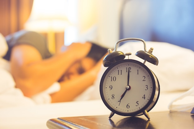 Man lying in bed turning off an alarm clock in the morning.