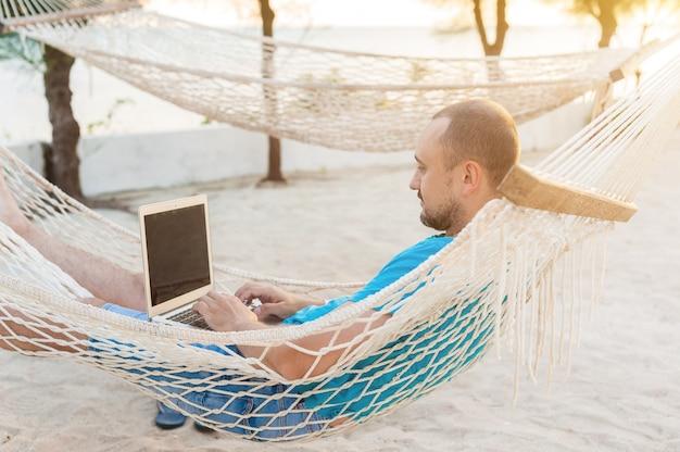 A man lying in a hammock overlooking the ocean