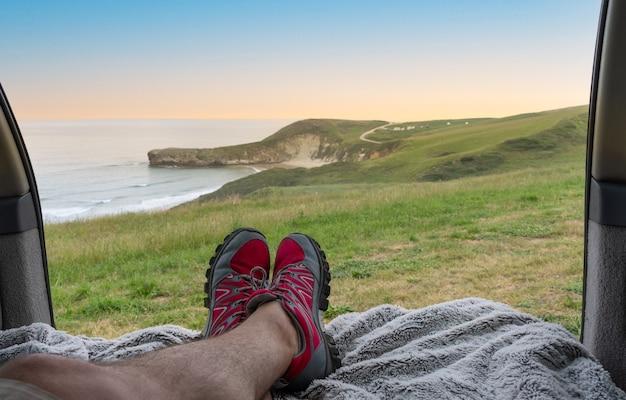 스페인 칸타브리아 해변 옆 언덕에서 일출을 바라보는 캠핑카에 누워 있는 남자.