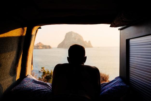 캐러밴에 누워 해변에서 일몰을 즐기는 남자