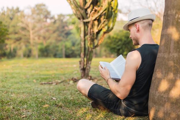 木に横たわっている男が本を読みます。帽子をかぶった観光客は、公園で本を読みます。男は本を読みます。リラクゼーションとアウトドアのコンセプト。