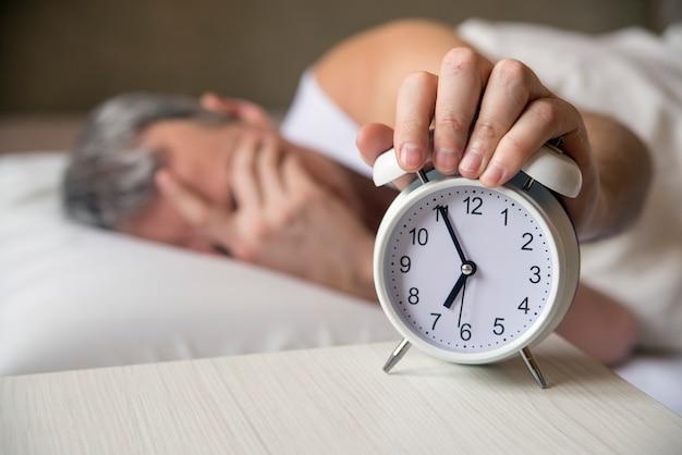 午前7時に午前中に目覚まし時計をオフにしてベッドに横たわっている男。寝室で眠っている魅力的な男。彼の寝室で目覚まし時計で目覚めた迷惑な男