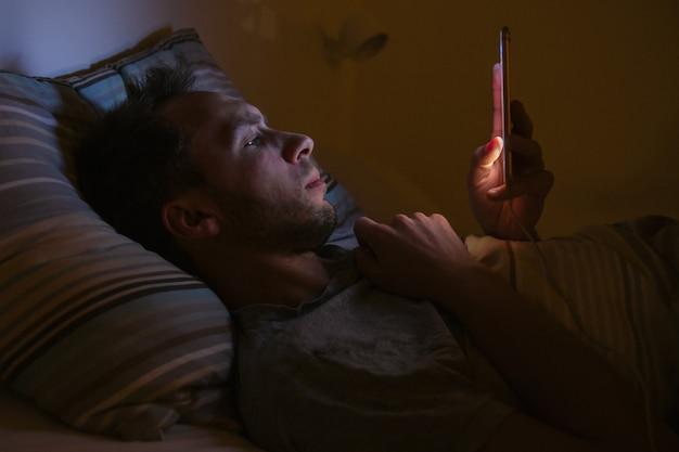 Человек лежал в постели с помощью смартфона в ночное время. бессонница, мелатонин, зависимость от социальных сетей