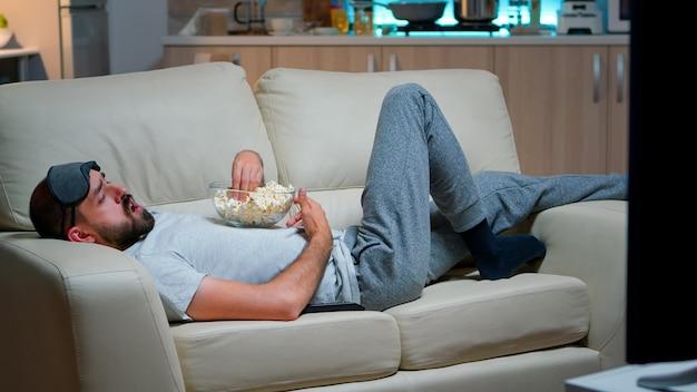 Человек, лежащий на диване, ест попкрон и смотрит телевизор