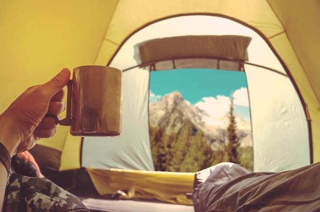 Мужчина лежит в палатке с кофе, вид на горы и небо из палатки. кемпер в спальном мешке, глядя на красивый пейзаж ранним утром