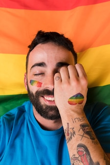 Man lying on lgbt flag