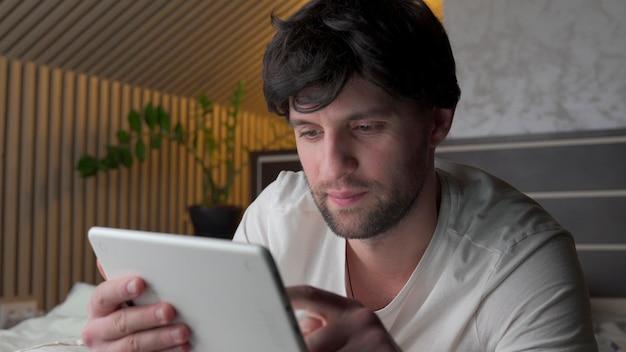 Человек лежал на кровати с помощью цифрового планшета.