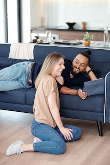 ソファに横になって、笑っているガールフレンドにタブレットコンピューターで面白いビデオを見せている男