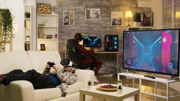 남자는 컴퓨터에서 노는 백그라운드에서 그의 여자 친구와 vr 헤드셋을 사용 하 여 비디오 게임을 하는 소파에 누워.