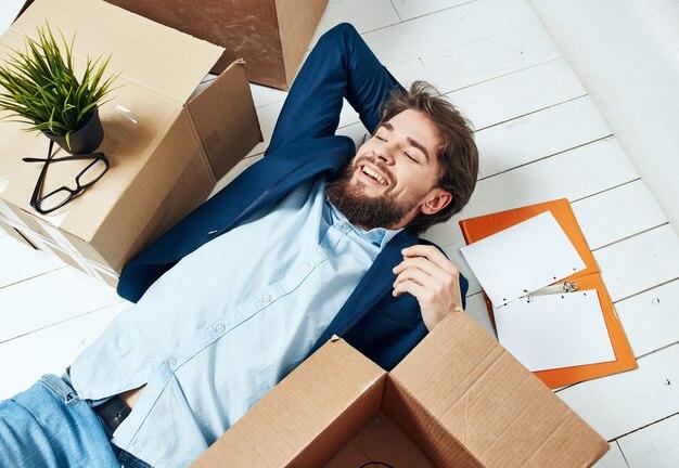 Человек, лежащий на полу с документами, офисная коробка с профессиональными вещами