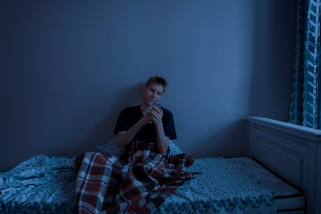 A man lying and using a smartphone before sleep, evening in the bed network addiction