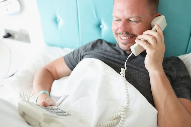 Man lying in white bed and calling on phone in hotel