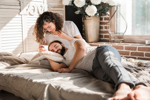 Man lying on woman's lap holding cup of coffee on bed at home