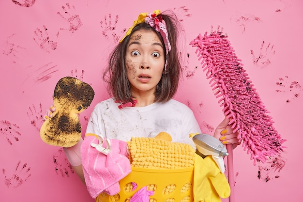 Man maid makes cleaning of house rubs dust with sponge holds dirty tools surprised to have much house work poses near laundry basket on pink