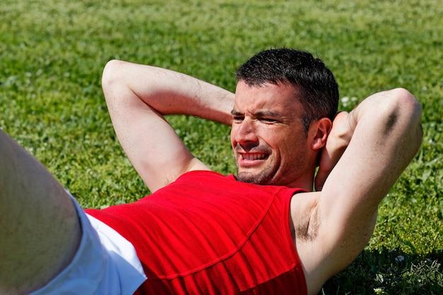 Человек делает упражнения на пресс в парке