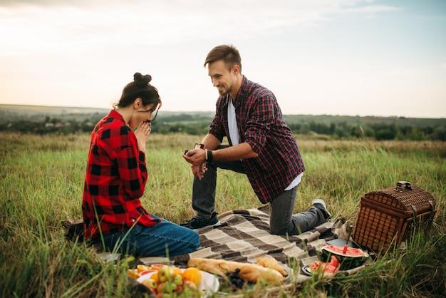男は夏の畑でロマンチックなピクニックに結婚の提案をします。男と女のジャンケット、幸せな瞬間