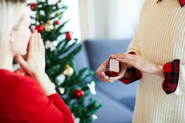 Мужчина делает предложение руки и сердца своей девушке в день рождества