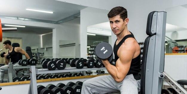 남자는 아령으로 운동을합니다.