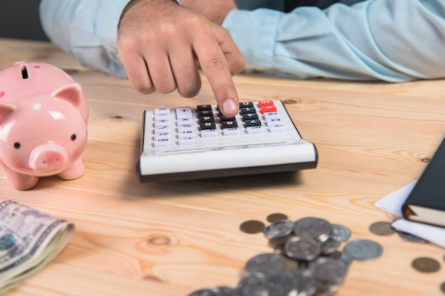 A man makes calculations and next to a piggy bank