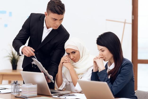 A man makes a claim to a woman wearing a hijab.