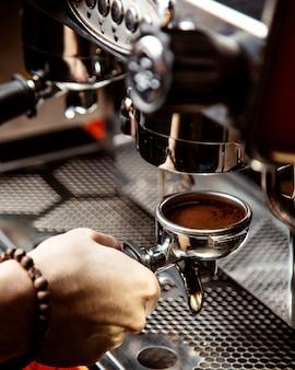 남자는 커피 머신에서 커피를 만든다