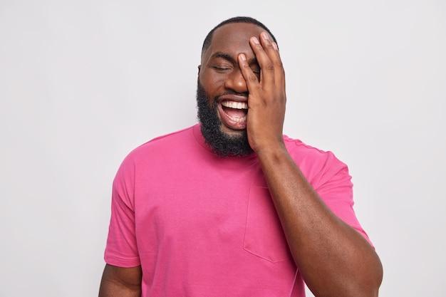 남자는 얼굴을 손바닥으로 눈을 감고 캐주얼 분홍색 티셔츠를 입은 평온한 미소를 흰색으로 재미있는 농담에 웃습니다.