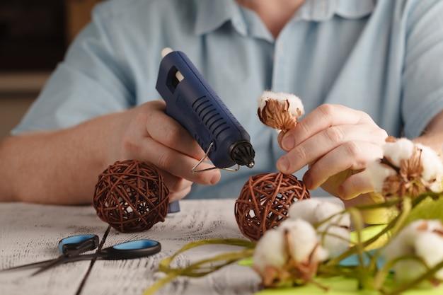 Мужчина делает цветочный декор с помощью пистолета-расплава