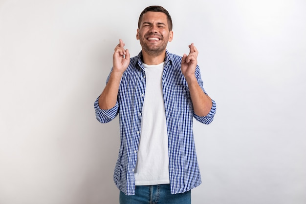 Man makes a gesture from crossing fingers in studio