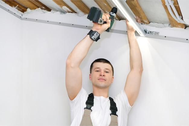 Человек делает ремонт дома. подготовка к установке натяжного потолка. установка светильников