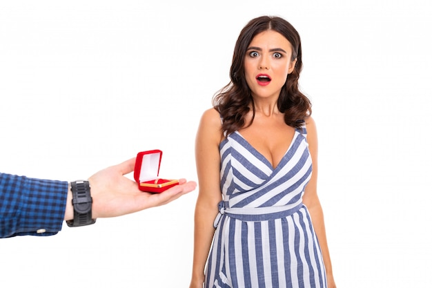 Man makes a proposal to a girl and gives a ring and a surprised girl in a dress on a white wall