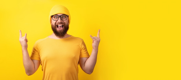 Man makes rock n roll gesture over yellow background, panoramic layout