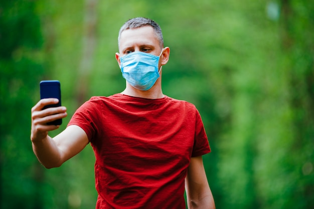 A man makes a selfie in a mask on a forest background