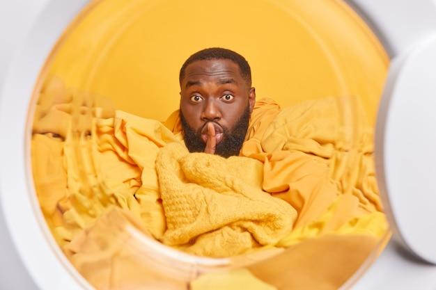 Человек делает жест тишины, держит указательный палец над губами, загружает стиральную машину грязным бельем