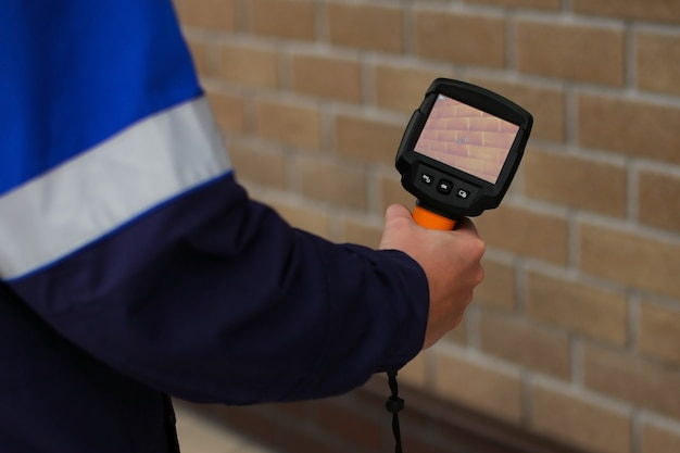 A man makes a thermal imager check with a camera, looking for heat leaks from the house.