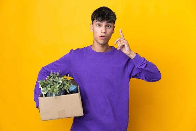 指を持ち上げながら解決策を実現しようとするものでいっぱいの箱を拾いながら動く男