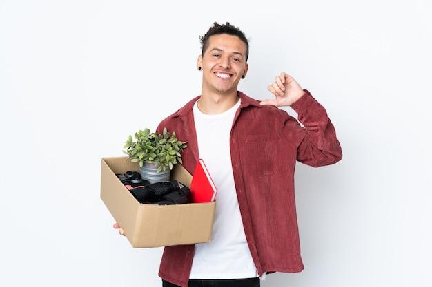 Человек делает движение, поднимая коробку, полную вещей над изолированным белым, гордым и самодовольным