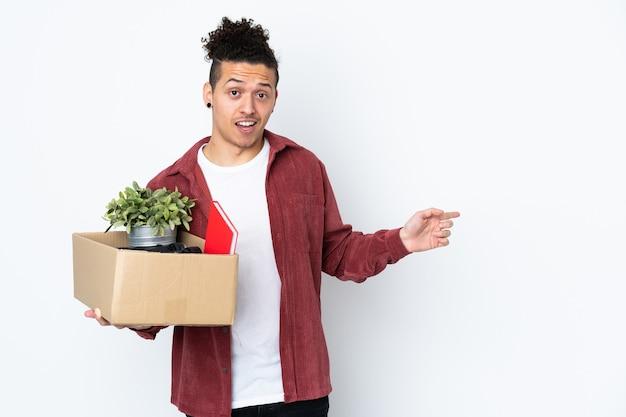 Человек делает движение, поднимая коробку, полную вещей над изолированным белым удивленным и указывая пальцем в сторону