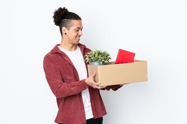 Человек делает движение, поднимая коробку, полную вещей на изолированном белом с счастливым выражением лица