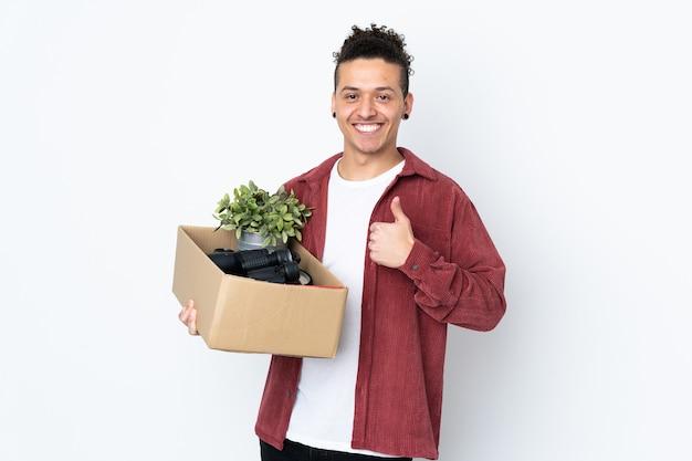 Человек делает движение, поднимая коробку, полную вещей на изолированном белом фоне, с поднятыми вверх большими пальцами, потому что произошло что-то хорошее
