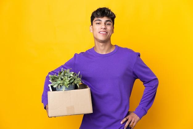 Человек делает движение, поднимая коробку, полную вещей, позирует с руками на бедрах и улыбается