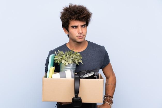 Человек делает ход, поднимая коробку с вещами, думая, идея