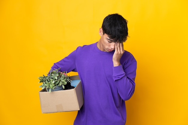 Человек делает движение, поднимая коробку, полную вещей с усталым и больным выражением лица