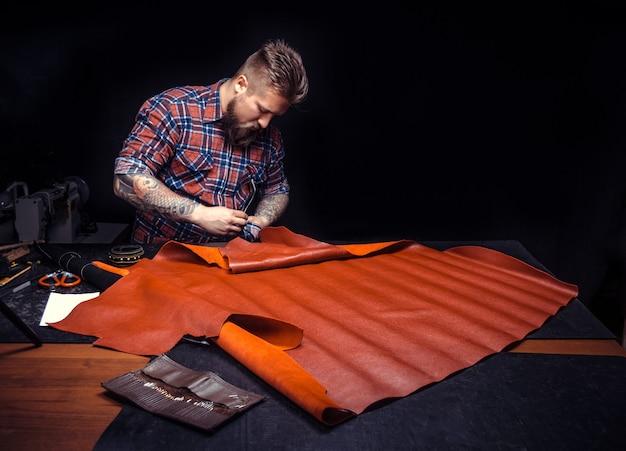 Человек делает сумку с кожей.