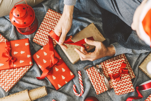 Man making bow from ribbon on gift