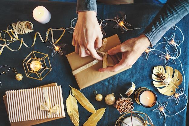Человек, делающий лук из ленты на подарок